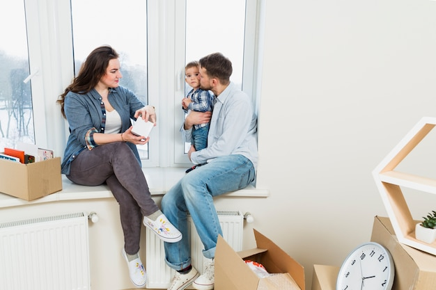 Młoda kobieta rozpakowywanie kartonów patrząc na jego mąż kochający syna