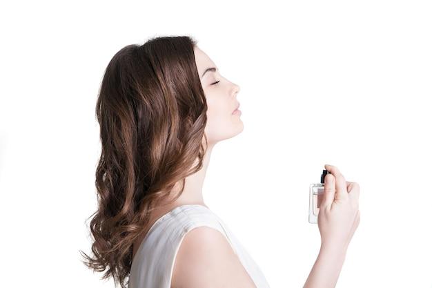 Młoda kobieta rozpyla perfumy na jej szyi