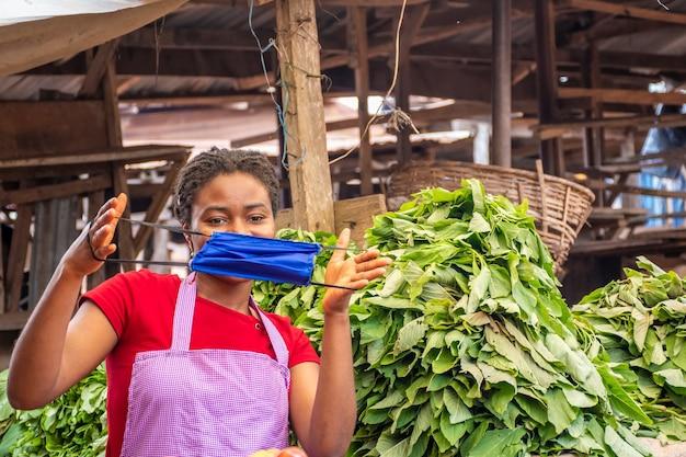 Młoda kobieta rynku afrykańskiego trzyma maskę na twarzy.
