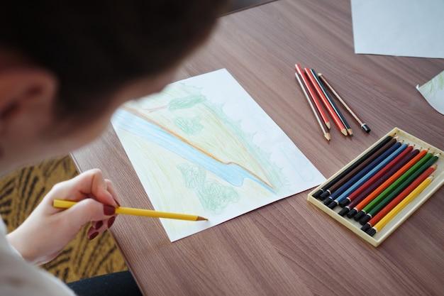 Młoda kobieta rysująca na papierze w domu, widok z góry