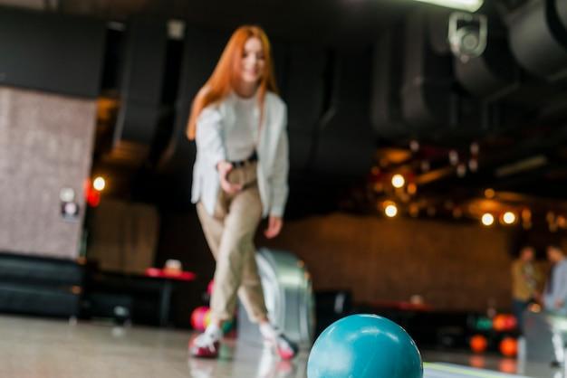 Młoda kobieta rzuca kula do kręgli