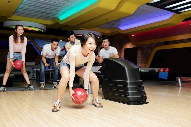 Młoda kobieta rzuca piłkę podczas gry w kręgle razem z przyjaciółmi
