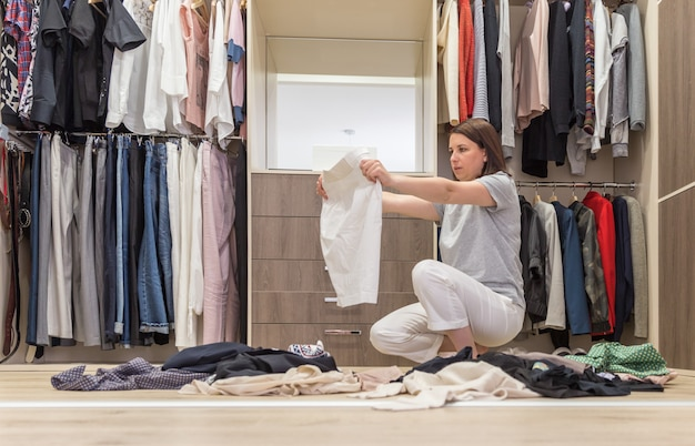 Młoda kobieta, rzucanie ubrania w spacer w szafie, bałagan w garderobie i garderobie