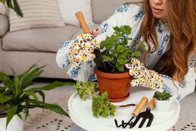 Młoda kobieta sadzenie w domu za pomocą narzędzi