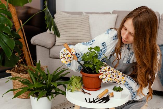 Młoda kobieta sadzi w domu