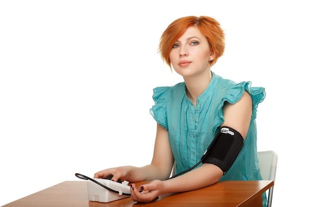 Młoda kobieta sama mierzy ciśnienie za pomocą tonometru na białym tle