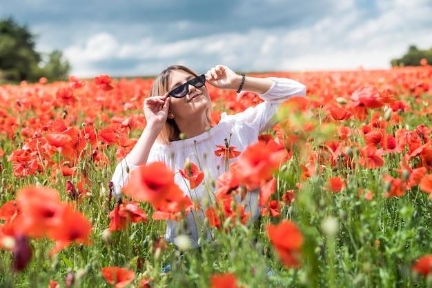 Młoda kobieta sama na mak w letni dzień pola