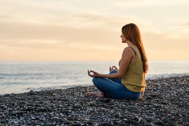 Młoda kobieta sama siedzi na piasku plaży o zachodzie słońca. pojęcie relaksu i medytacji