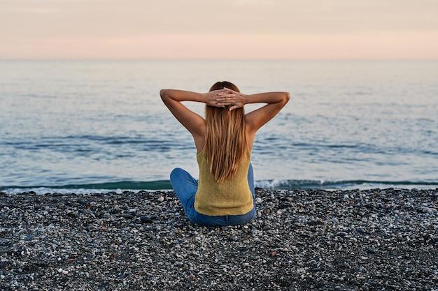 Młoda kobieta sama siedzi z otwartymi ramionami na piasku plaży o zachodzie słońca. pojęcie relaksu, medytacji i wolności.