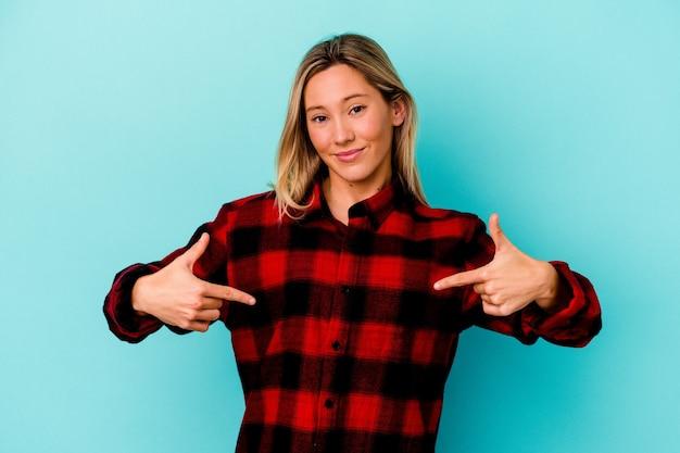 Młoda kobieta samodzielnie na niebieskiej ścianie osoba, wskazując ręką na przestrzeni kopii koszuli, dumny i pewny siebie