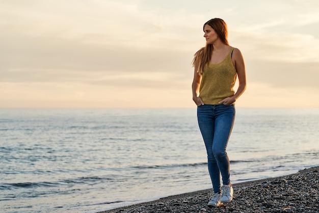 Młoda kobieta samotnie spacerując po piasku na plaży o zachodzie słońca. pojęcie relaksu i medytacji