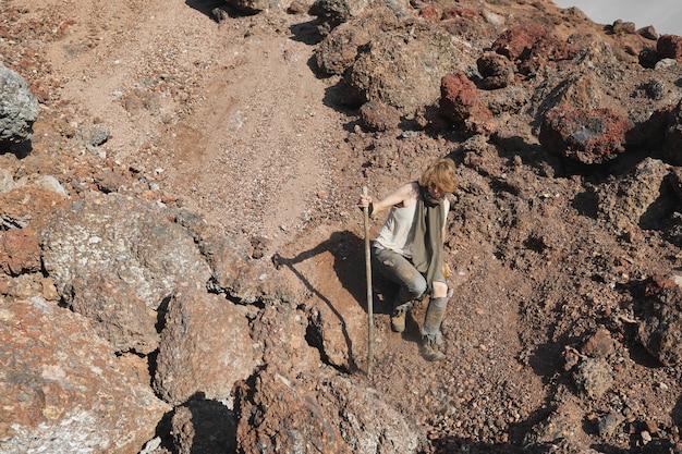 Młoda kobieta schodząca z kamiennej góry za pomocą kija