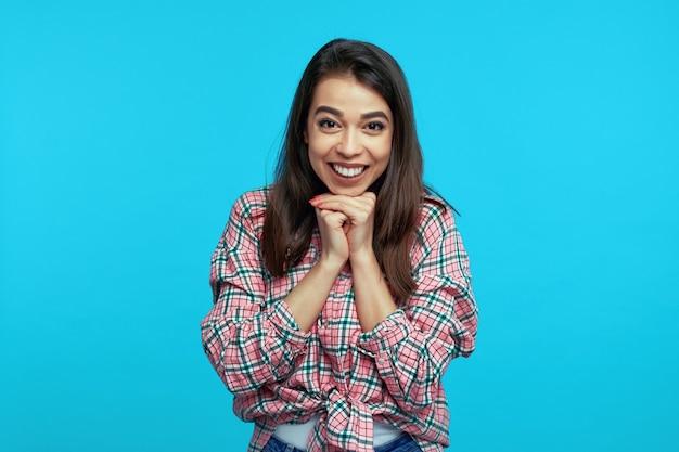 Młoda kobieta ściska dłonie w pobliżu twarzy, uśmiecha się szeroko na niebieskiej ścianie