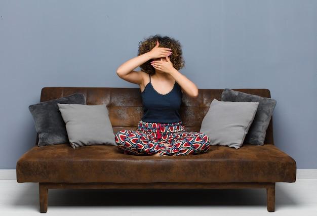 Młoda kobieta ściska twarz obiema rękami, mówiąc nie! odmawianie zdjęć lub zakaz robienia zdjęć siedząc na kanapie.