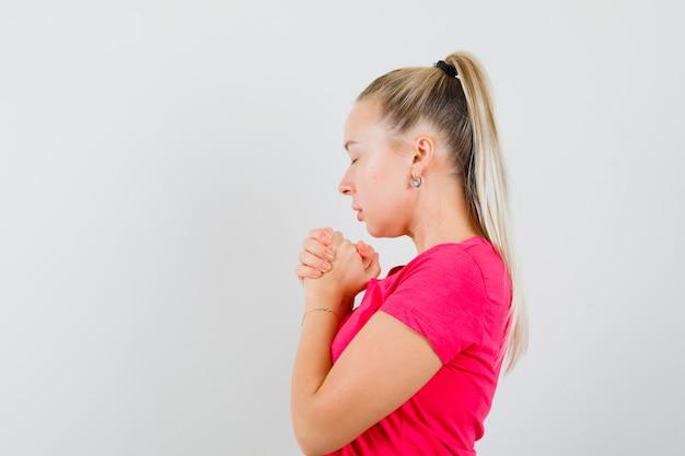 Młoda kobieta, ściskając ręce w geście modlitwy w różowej koszulce i patrząc z nadzieją
