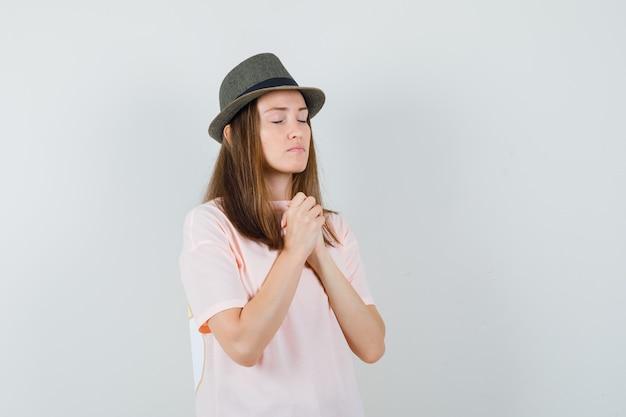 Młoda kobieta, ściskając ręce w geście modlitwy w różowej koszulce, kapeluszu i spokojnym spojrzeniu. przedni widok.