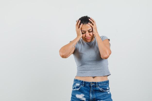 Młoda kobieta ściskająca głowę w dłonie w t-shirt, szorty i wyglądająca na zmęczoną.