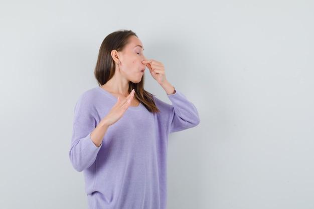 Młoda kobieta ściskająca nos w liliowej bluzce i wyglądająca na zniesmaczoną