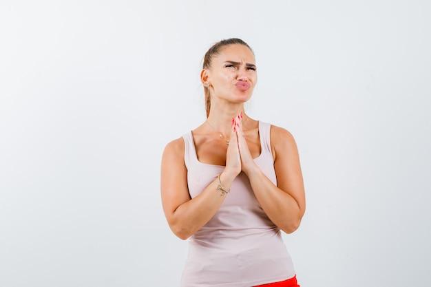Młoda kobieta ściskająca ręce razem do modlitwy w podkoszulku i wyglądająca na zaniepokojoną. przedni widok.