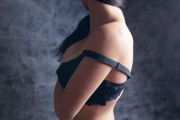 Młoda kobieta seksualnie zdejmuje stanik