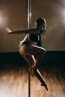 Młoda kobieta sexy pole dance, ciemne tło