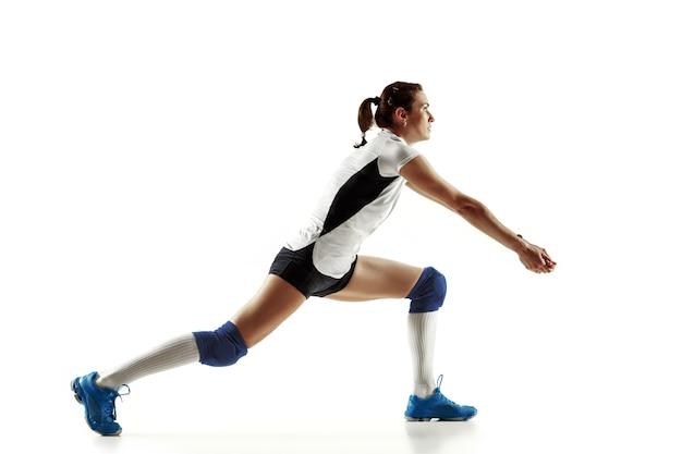 Młoda kobieta siatkarz na białym tle na białej ścianie. kobieta w sportowym sprzęcie i butach lub trampkach, trenuje i ćwiczy. pojęcie sportu, zdrowego stylu życia, ruchu i ruchu.