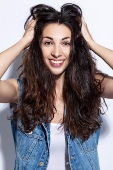 Młoda kobieta się śmieje. piękna brunetka w dżinsach z długimi włosami. pozytywność i szczęście. białe tło. zbliżenie.