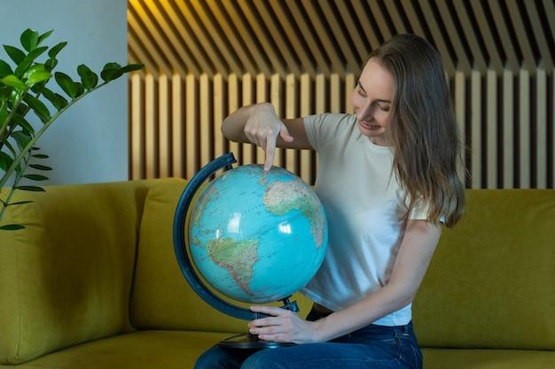 Młoda kobieta siedząc na kanapie w domu trzymając kulę ziemską świata wybrać trasę podróży