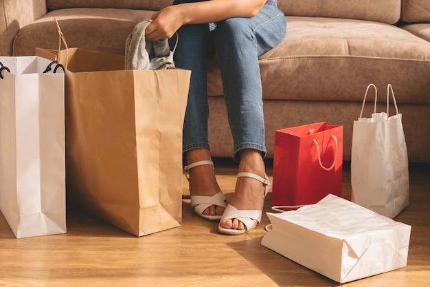 Młoda kobieta, siedząc na sofie, wyjmuje zakupy z torby