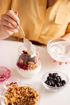 Młoda kobieta, siedząc przy stole i robiąc sobie śniadanie, dodaje do szklanki świeżą kwaśną śmietanę z jogurtem