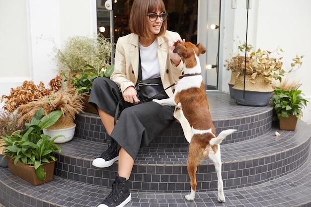 Młoda kobieta siedząca na schodach trzyma psa na smyczy, w pobliżu jest jej uroczy pupil terier jack russell
