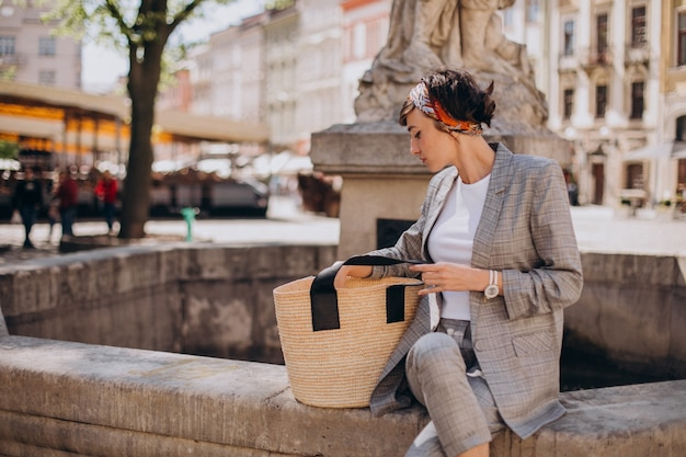 Młoda kobieta siedząca przy fontannie