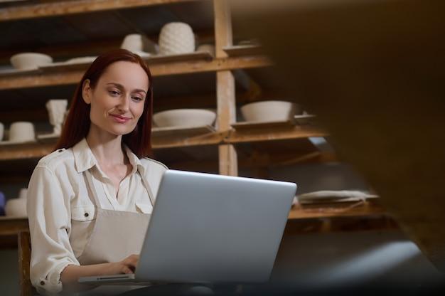 Młoda kobieta siedząca przy laptopie w warsztacie garncarskim