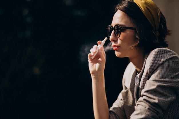 Młoda kobieta siedzi i palenia papierosów