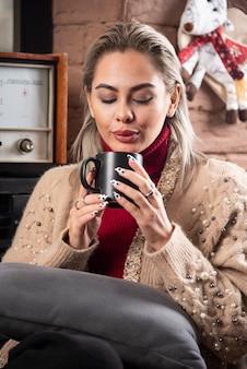 Młoda kobieta siedzi i pije gorącą herbatę