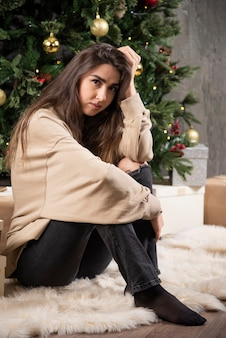 Młoda kobieta siedzi i pozuje w pobliżu choinki.