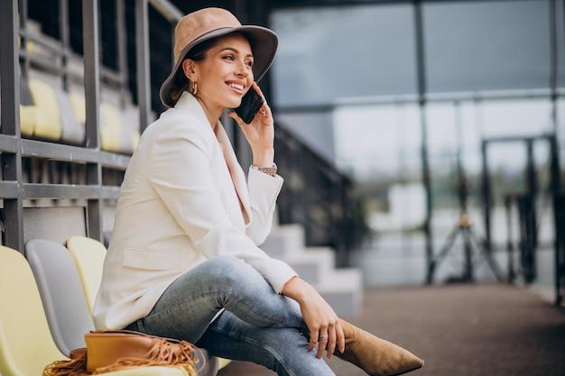 Młoda kobieta siedzi na arenie i rozmawia przez telefon