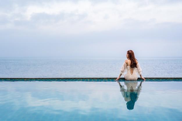 Młoda kobieta siedzi na brzegu basenu i patrząc na morze