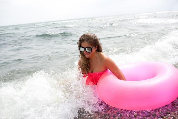 Młoda kobieta siedzi na brzegu morza lub oceanu w falach z różowym dmuchanym materacem w dłoni i ciesz się.