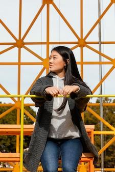 Młoda kobieta siedzi na budowie mostu