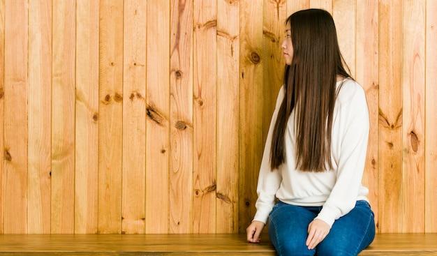 Młoda kobieta siedzi na drewnianym miejscu, patrząc w lewo, z boku stanowią