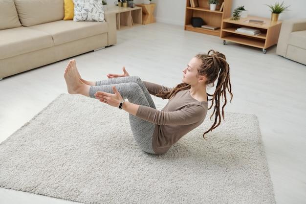 Młoda kobieta siedzi na dywanie pośrodku pokoju, trzymając nogi ugięte w kolanach i ręce blisko kostek