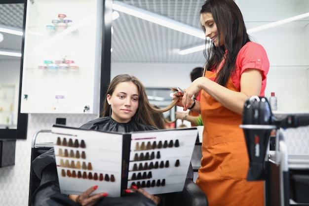 Młoda kobieta siedzi na fotelu fryzjerskim i trzyma w dłoniach katalog z paletą kolorów dla...