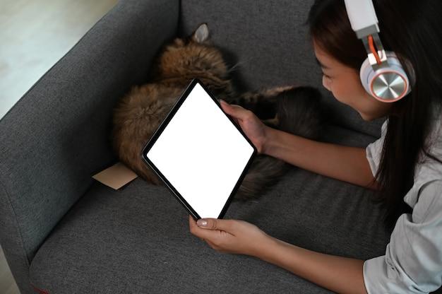 Młoda kobieta siedzi na kanapie i ogląda coś na tablecie.