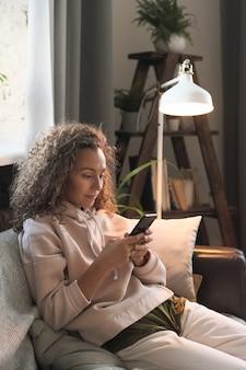 Młoda kobieta siedzi na kanapie i pracuje online przy użyciu swojego telefonu komórkowego w domu