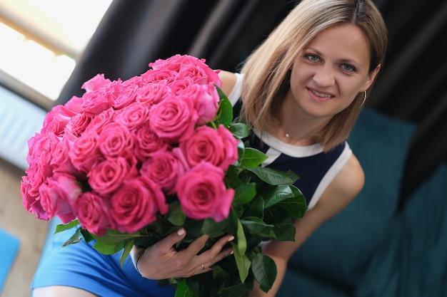 Młoda kobieta siedzi na kanapie i trzyma duży bukiet róż