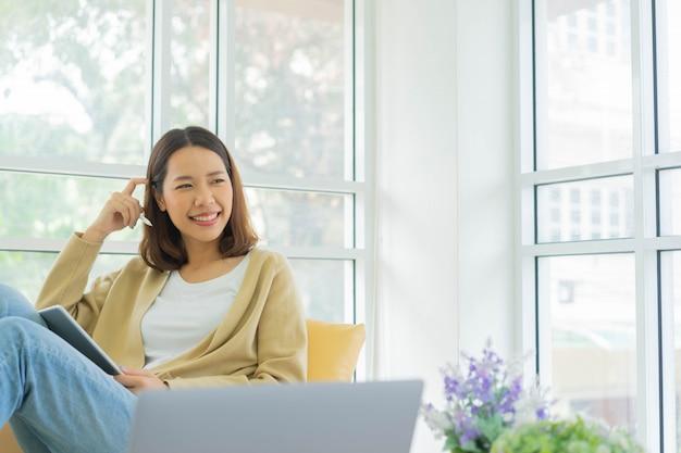 Młoda kobieta siedzi na kanapie, myśląc o wykładzie w domu na kwarantannie koncepcji stylu życia