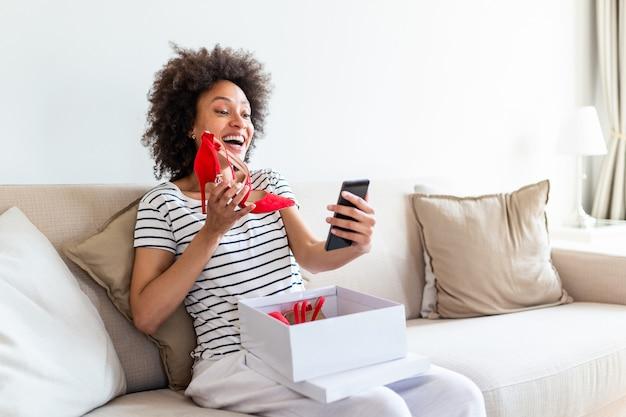 Młoda kobieta siedzi na kanapie w domu i taktowanie twarzy, aby pokazać jej nowe buty
