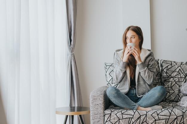 Młoda kobieta siedzi na kanapie w swetrze popijając kawę lub herbatę z białego kubka rano w sezonie zimowym, patrząc na zewnątrz