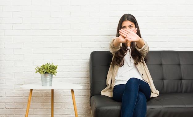 Młoda kobieta siedzi na kanapie, wykonując gest odmowy